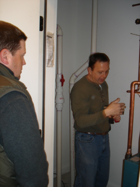 Home inspector Kevin Fulara explains the radiant heat boiler to buyer Brad Krauss